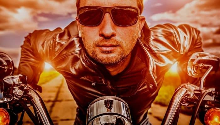 man with sunglasses leaning forward on motorcycle