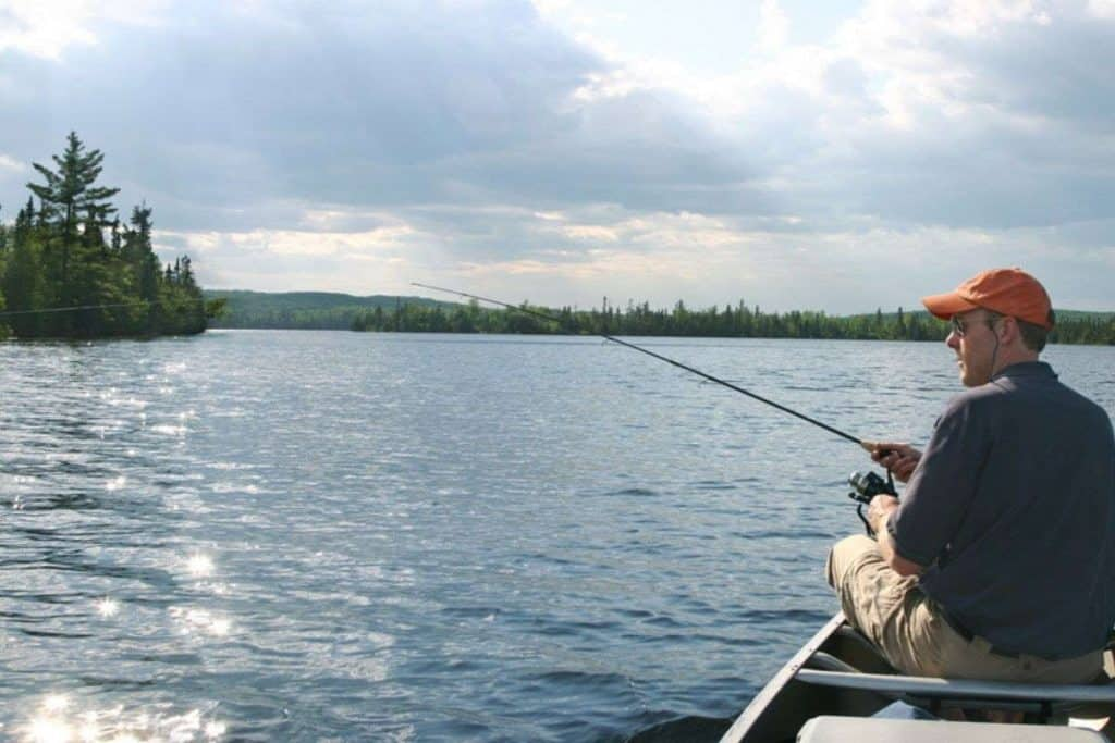 man fishing on top of canoe