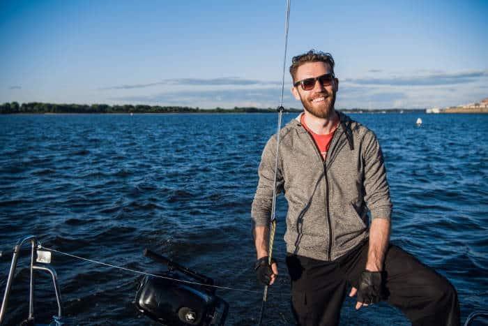 smiling man sailing on catamaran