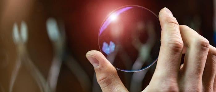 closeup hand holding glasses lens