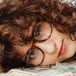 woman in glasses lying on money